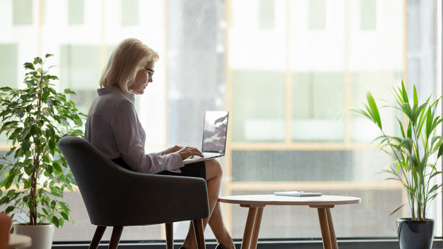 60s businesswoman put laptop on lap typing business message