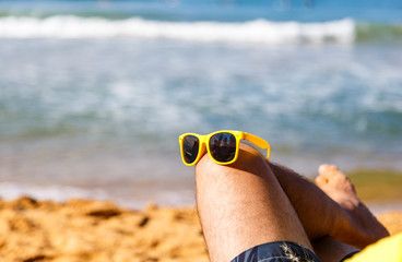 stylish yellow sunglasses on a man's knee against the background of a sandy beach and the sea. Concept of holiday resort.