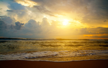 Reflection of vivid sunset sky over sea and beach.Colorful sunrise with Clouds over ocean. Pink and yellow sunset over the ocean with clouds, Sri Lanka, Asia, Ceylon