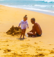 little kid girl and his father building sandcastle on the sandy shore of a tropical beach, Sri Lanka, ocean waves in background