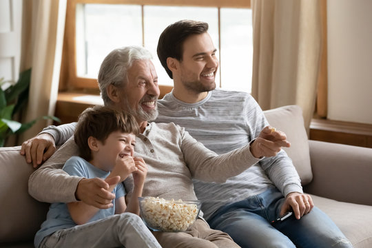 Happy three generations male family watching football championship match.
