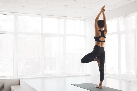 Woman exercising yoga in tree pose at home