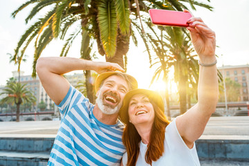 Adult couple dating and taking a selfie in Barcelona at sunset