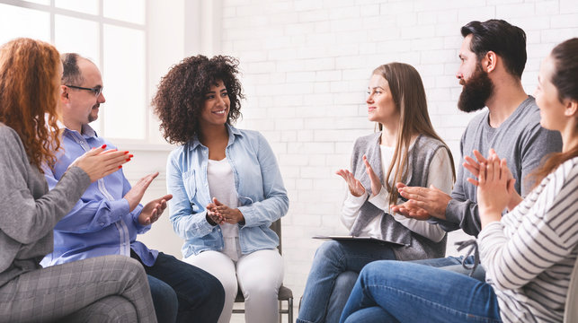 Diverse people applauding to themselves at therapy session in rehab