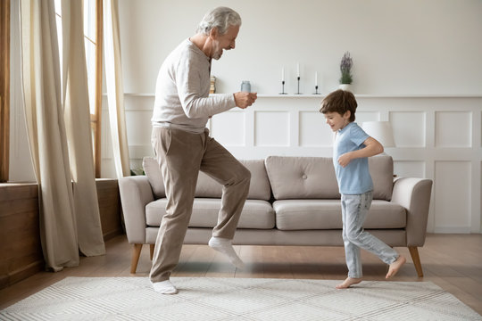 Overjoyed older senior grandfather dancing with excited little grandson.