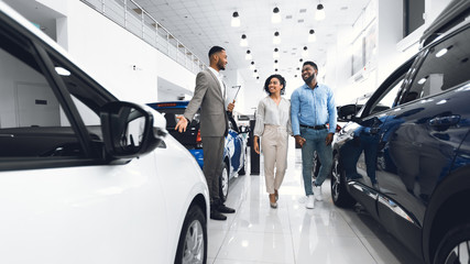 Car Sales Manager Showing Auto To Buyers In Dealership Store