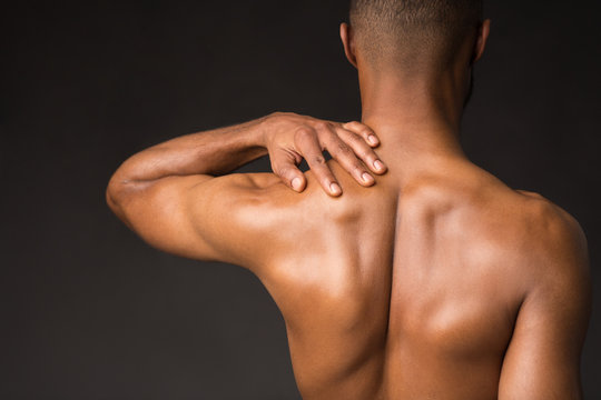 Shirtless black man doing neck and shoulder massage