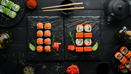 Set of colored sushi in black plates. Japanese food. Top view. Free space for your text.
