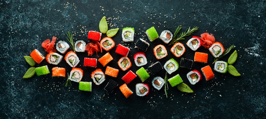Big set of pieces of sushi rolls on black stone background. Top view. Free space for your text.
