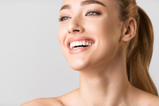 Beauty Portrait Of Millennial Girl Laughing On Gray Studio Background