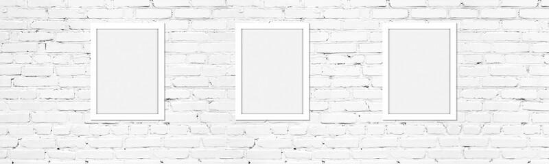 Blank white photo frames on light whitewashed brick wall