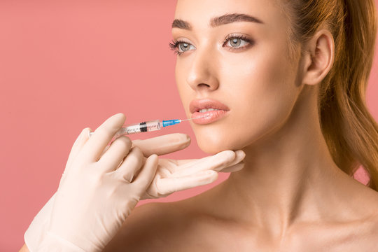 Pretty Girl Receiving Beauty Injection In Lips Over Pink Background