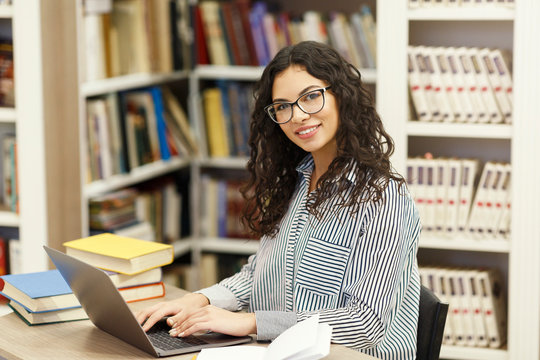 Cheerful latina girl sitting at desk in modern library