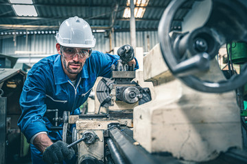 Male worker in blue jumpsuit and white hardhat operating lathe machine.