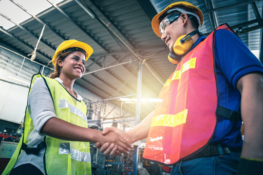 Female supervisor shaking hand with male site engineer.