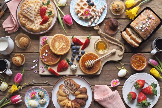 Easter festive dessert table with various of cakes,  pancakes, waffles and sweets.