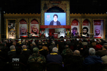 Lebanon's Hezbollah leader Sayyed Hassan Nasrallah addresses his supporters through a screen during a rally in Beirut's southern suburbs