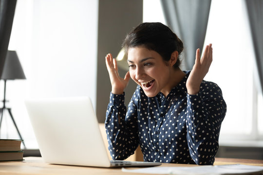 Excited indian girl amazed with good online news