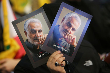 A supporter of Lebanon's Hezbollah leader Sayyed Hassan Nasrallah carries pictures of the late Iran's Quds Force top commander Qassem Soleimani during a rally commemorating in Beirut's southern suburbs