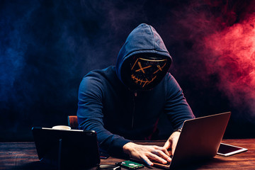 young criminal male hides his face under the hood and mask, hacks the password on the laptop, typing something. anonymous, incognito guy going to hack. cyberattack concept - fototapety na wymiar