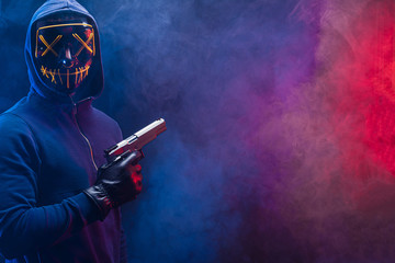 Male hoodie hacker wearing mystery mask hold gun in hands. cyber attack or internet security concepts. young unrecognizable anonymous thief committing the crime isolated in smoky space