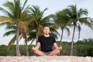 Obraz Young yoga man wearing black t-shirt at the beach, relaxing, breathing and meditating in a natural environment with palm trees and ocean as background.  - fototapety do salonu