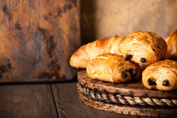 Freshly baked sweet buns puff pastry with chocolate and croissants on old wooden background. Breakfast or brunch concept with copy space. Fototapete