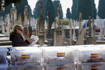 A woman stands next the boxes containing the remains of 245 people killed by the late Spanish dictator Francisco Franco's forces during the civil war are seen in Valladolid