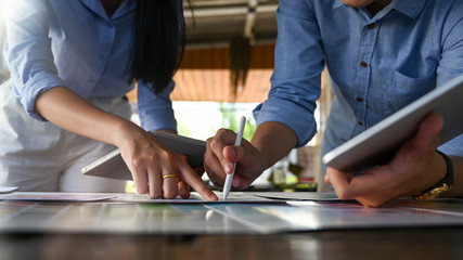 Cropped image of young graphic designer team holding/using a stylus pen and computer tablet while planning/brainstorming/discussing about their new project design at the modern meeting table.