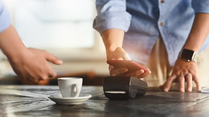 Cropped image of man using a smartphone for making a bill payment at credit card reader with the cafe cashier counter as background. NFC technology concept.