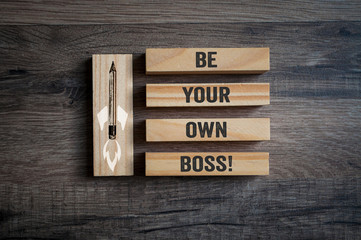 Pieces of wood  with pencil rocket and message Be your own boss on wooden background