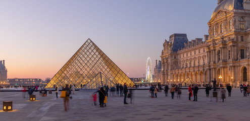 PARIS, FRANCE - DECEMBER 31, 2019: The Louvre museum pyramid at sunset in Paris on December 31, 2019. Completed in 1989, the large pyramid serves as the main entrance to the Louvre Museum.