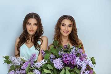 Studio fashion portrait photo of two twins women with a bouquet of spring flowers