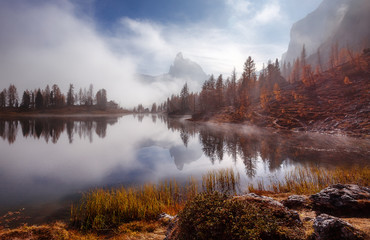 Fotomurales - Amazing Scenery of nature with morning fog. Magical Mountain lake Federa in Dolomites Alps glowing sunlit. Wonderful picturesque Scene at Autumn Highlands. Postcard. Awesome Sunny Landscape.