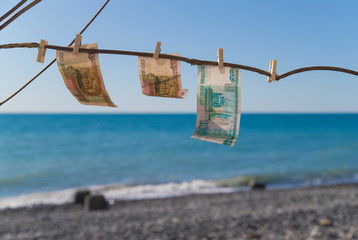 Poster Zanzibar banknotes hanging against the background of sea. clothespins. the concept of preparing to vocation. holidays by the sea. rubles