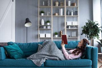 Happy woman with a book in her hands resting on a cozy sofa at home. Wall mural