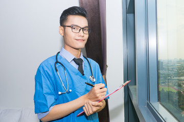 Young Asian doctor writing his medical report and look to the camera