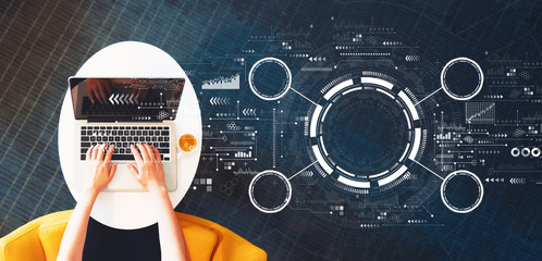 Wall Mural - Tech circle with person using a laptop on a white table