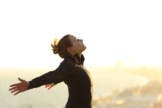Runner relaxing breathing fresh air outstretching arms