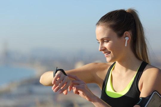 Runner wearing earbuds checks music on smartwatch