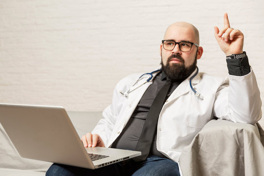 A male doctor in a white coat is sitting on a sofa with a laptop. Blogging and coaching.