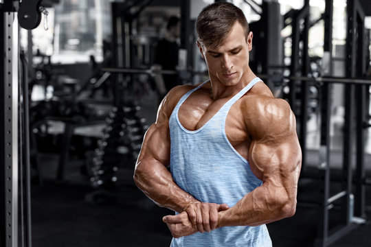 Muscular man showing muscles in gym. Strong male bodybuilder