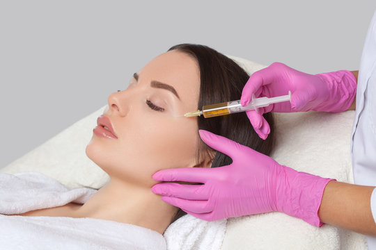 Cosmetologist does prp therapy anti wrinkle and aging skin on the face of a beautiful woman in a beauty salon. Cosmetology concept.