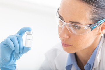 A young female scientist is researching a chemical substance using protective glasses and hygienic gloves