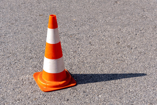 A orange and white plastic traffic cone used to communicate that a road or street is not currently accessible due to, for example, ongoing road work, construction, a roadside accident or danger.