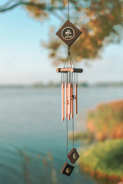 a wind chime meaning water element. summer lake on blurry background