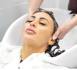 Girl with closed eyes washes her hair in beauty salon