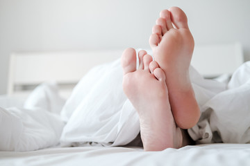 Men's feet under a white blanket, in bed, in a comfortable apartment, in natural light, with copy space.