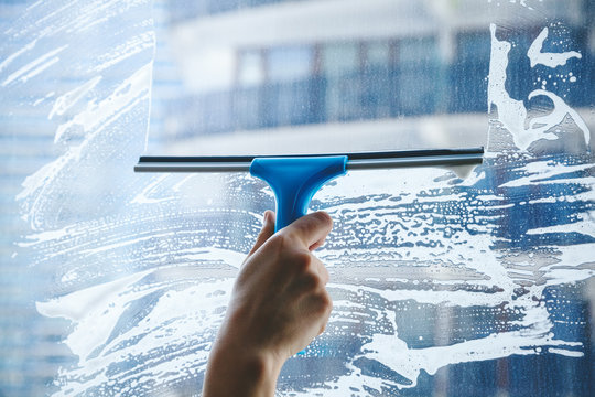 young female hand cleaning dirty glass window with a squeegee
