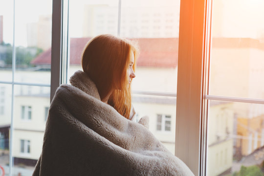 thoughtful calm pensive young woman looking through the window at home wrapped in warm comfy blanket